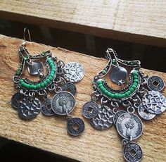 Expand your unique jewelry with Eclectic Medallion Edition Earrings. These earrings are beautiful with silver exotic coins and light green beading