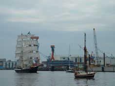 Sailing ship with two masts in full sail entering Kiel harbour.