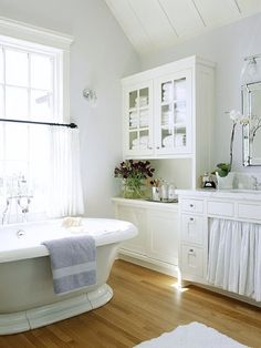 Beach House Bathroom - Though they can be more expensive than store-bought bathroom cabinets, built-ins offer custom storage options. In this room, a wall of built-ins, including a linen press-style cupboard, transform the space into a charming, functional bath without taking up much floor space