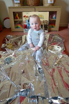 Large foil blankets are cheap and make a great noise as well as being reflective. Let babies crawl and explore all over them.