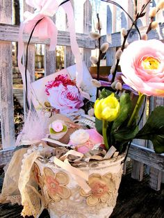 Grownup girls love Easter baskets too! MY version is made in a large size peat pot that I have whitewashed and added a wire handle. Next comes the beautiful vintage lace covering, that has raised flowers with a soft pink center.The treasures inside the Vintage shredded paper grass,