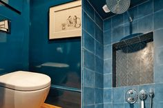 The blue lacquer powder room has a shower that features Popham Design tiles that were made by hand in Marrakesh.