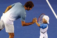 Roger Federer of Switzerland high fives Cruz Hewitt, the son of Lleyton Hewitt of Australia, during the Kids Tennis Day before the Australian Open 2014 tennis tournament in Melbourne, January 11, 2014. [Photo/Agencies]
