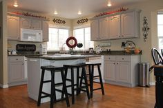 wood floors, painted cabinets, white appliances