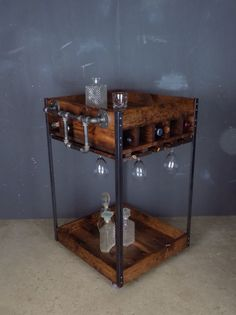 Industrial bar cart made of pine, steel and black pipe with casters in a Red Oak finish.