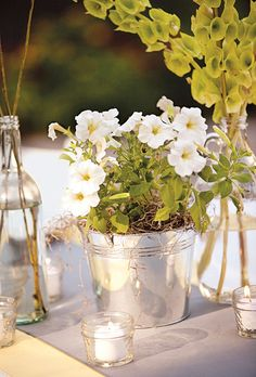 Tin pails full of white flowers, bells of Ireland in antique milk jugs, and glass bottles filled with craspedia, all atop yellow and gray table runners. Photo by Akil Bennett.