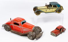 """Lot 465: British and French Metal Toy Cars; Three wind-up vehicles including a red roadster marked """"British Made,"""" a beige and blue car marked """"Made in England"""" and a French """"2002"""" wind-up gangster car"""
