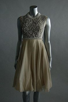 ~A Madame Grès grey chiffon cocktail gown, late 1950s, labelled and with additional atelier tag `Mme Marguerite, Katia no 8078', the bodice front covered with silver and white bugle beads, studded with rhinestones, transparent back bodice, layered chiffon skirt over silk jersey ground~