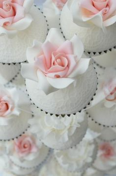 stunning cupcakes : white-on-white patterned icing, topped with white and soft pink flower.