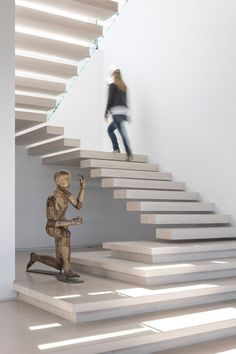 Light colored, stone floating stairs with a space for a sculpture, lead you upstairs in this home.