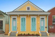 New Orleans Cottage For Sale is bright yellow with turquoise shutters and door. Historic cottage with exposed brick fireplaces and plenty of modern updates. Yellow House Exterior, House Paint Exterior, Interior Exterior, Exterior Colors, Yellow Cottage, Old Cottage, Cottage Homes, Villas, Exposed Brick Fireplaces