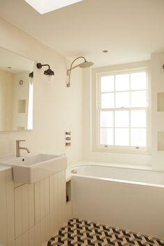 Kid's Bathroom. Duravit semi recessed basin. Tap by Aston Matthews. Shower head by Boffi. Corian bath surround and shelves. Lighting and mirror John Lewis. Geometric concrete floor tiles.