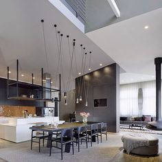Open plan spaces are all the rage – it's the #home layout that everyone is after. So check out this #jawdropping combination of #kitchen, #diningroom and #livingroom with plenty of #dark hues! #Design by Ippolito Fleitz Group. Check out homify.com! #homify #interior #interiordesign #moderndesign #moderninterior #modernliving #moderndiningroom #elegantdiningroom #fireplace #lamps