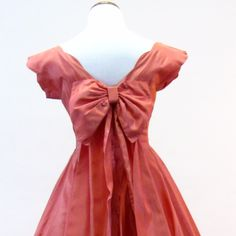 Item Detail: 1950's party dress. Scalloped boat neckline, cap sleeve, fitted through the waist with a big full skirt and tulle underskirt. Material: Taffeta Condition: OK. Some holes in the tulle unde