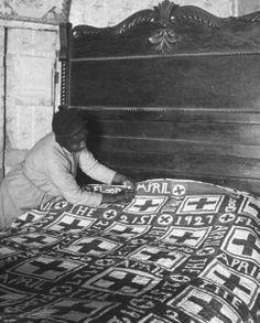 "Sharecropper Lizzie Alexander mending the ""Red Cross"" quilt she made to commemorate the terrible flood of 1927 (quilt is displayed on bed with huge wooden headboard, in her farm house in rural Mississippi) 1937, Photo by Alfred Eisenstaedt"