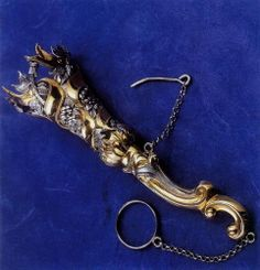 .A tussie mussie is a funnel-shaped container for holding a posy (a nosegay). The handle may be of ivory, amber, porcelain, mother-of-pearl. The posy is secured by a pin across the mouth of the funnel and the holder is attached to a dress by a pin or hook. Some have a finger ring attached by a chain for use when held by hand. The name 'tussie' originates from an old English word for a nosegay. The second part refers to the wet moss used to keep the flowers moist. Porcelain Jewelry, China Porcelain, Bouquet Holder, Nosegay, Luxury Purses, Antique Jewelry, Two By Two, Fashion Accessories, Nostalgia