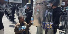 Photo shows little boy handing water to riot police in Baltimore