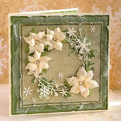 handmade Christmas card with a wreath of die cut and punched pieces ... snowflakes, flourishes, layered poinsettias .. shabby chic styling ... light greens and vanilla ... great for display ...