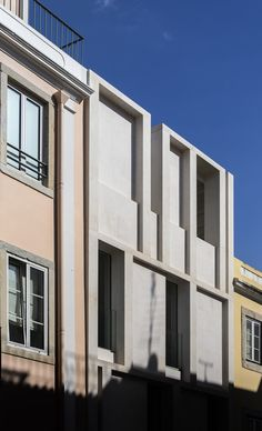 A raw concrete interior is contained behind the white limestone facade of this townhouse in Lisbon.