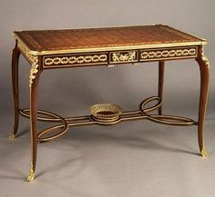 FRANÇOIS LINKE A Fine Mahogany and Marquetry Centre Table France, ca 1890  With Gilt-Bronze Mounts  This fine marquetry table has a frieze with a gilt-bronze foliate meander centered by a tablet embellished with finely cast gilt-bronze mounts depicting bacchanalian cherubs at play. The cabriole legs with gilt-bronze mounts and sabots are united by an interlaced stretcher surmounted by an open-work gilt-bronze basket in the manner of Weisweiller.