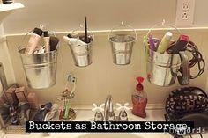 Buckets as bathroom storage.