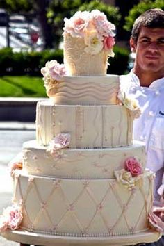 Amazing huge wedding cake, decorated with light pink ribbon and shades of pink flowers. - From www.elegantcheesecakes.com