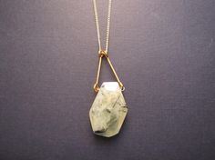 Lime prenite stone pendent with brass bars on a gold plated curb chain