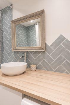 Pose à bâton rompus de faïence bleu gris sur le mur d'une salle de bain au top de la tendance. Réalisé par Little Worker.