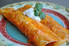 Shredded Chicken Enchiladas with red sauce  Olive oil   1 c white onions, chopped   2 sm cloves fresh garlic, minced   4 c cooked chicken, shredded   1 tbsp red chile powder   2 tbsp cumin   Kosher salt   2-3 cans enchilada sauce   12 flour tortillas   2 c grated cheese     Preheat the oven to 350 degrees F