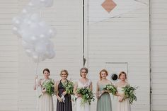 Bridesmaids in neutral dresses with big, green bouquets (and balloons!)