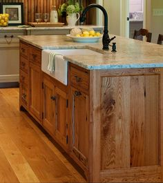Substantial wood kitchen island with apron sink, single-handle rubbed bronze tall faucet.