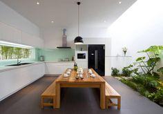 Cocina-comedor de casa vietnamita con jardín tropical interior, pared cocina verde menta • Tropical garden in a House in Vietnam | Photo:Nam Bui