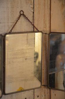 """Miroir de barbier Miroir de barbier avec sa chainette pour accroche au mur. Miroir """"dans son jus"""", traces d'usure. Dos en cuir bordeaux."""