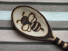 This wooden spoon has stripes up the handle, a bumble bee on one side and a flower on the other.  It has been scorched into the wood by the