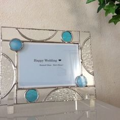 ◆ステンドグラス製のフォトフレームです。ハンドメイドで丁寧に仕上げました。爽やかな水色2種類の硝子のドットが涼しげです♫クールなガラスですが、ハンドメイドの温かみを感じて頂ければ幸いです。◆ご結婚祝い、お誕生日のプレゼント、ご出産祝い、新築祝い。。。    様々なシーンの贈り物にお遣い下さいませ。❤︎ラッピングは水色のペーパーに、シールリボンになります。(画像参照)◆安定感のあるアクリルのスタンドで、Lsizeのお写真を、縦横どちらにも飾れるデザインです。◆サイズ         縦   14.5cm      ×       横   18.5cm