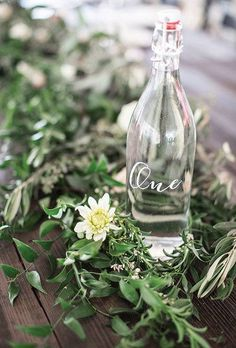Easy Spring Centerpieces clear bottle and green filler centerpiece-- bottle doubles as water service and table number -- genius! Set amidst a scattered bunch of filler greens.