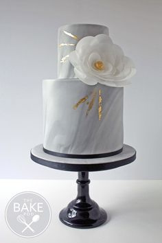 A marble effect two tier wedding cake decorated with gold leaf and a pretty, edible wafer paper flower #marbleweddingcake #waferpaperflower #ediblewaferpaperflower #goldleaf