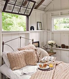 Treehouse Room  - West Elm linens adorn this tree house's antique iron bed. Neutral tones and rustic touches, like pinecones and binoculars, compliment the surrounding woodland exteriors and raw branch supports overhead.