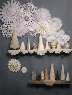 Ethereal Display ~ tissue snowflakes and handcut paper snowflakes on the wall, strung through with a few crystal garlands for sparkle.  Vintage doilies and trees on the shelves.