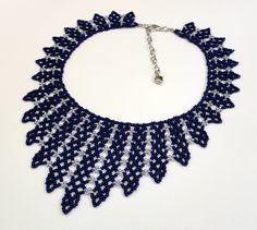 Colar confeccionado com miçangas azul escuro com cinza brilhante. Acabamentos em metal niquelado. Comprimento: 35 cm + 7 cm de corrente extensora Largura no meio do colar ( bico): 8 cm