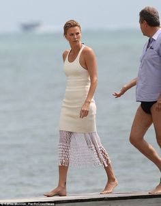 Interesting attire: Charlize was seen chatting to a man wearing skimpy swimming trunks as they walked along a wooden platform