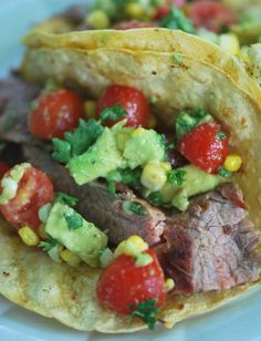 Steak Tacos with grilled corn,tomato, and avacado salad.  Super yummy summertime dinner. This was great! We didn't make the honey lime dressing. I put lime juice, Valentina's hot sauce and jalapeños on mine; Nick put ranch on his. Either way, it's a hit.