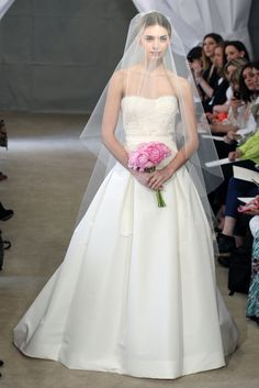 Carolina Herrera Primavera Verano 2013. Vestido de cuerpo palabra de honor bordado con encajes y falda lisa con volumen. El punto sofisticado lo añade el velo a medio cuerpo y el bouquet rosa.