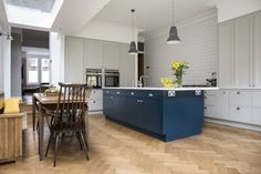 Hand painted kitchen island in Hague blue and yellow breakfast cabinet with walnut interiors.
