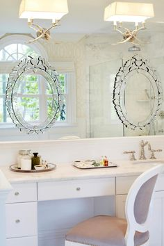 Ornate Venetian mirrors are glued over a larger mirror to provide a continuity of reflective effect, creating depth in the master bathroom. A custom white and light gray linen chair sits beneath two sleek white scones and a smooth, white vanity space.