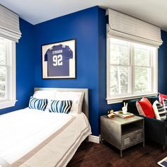 Royal blue bathes the walls of this kid's bedroom, a vibrant backdrop for treasured collectibles and fun patterns.