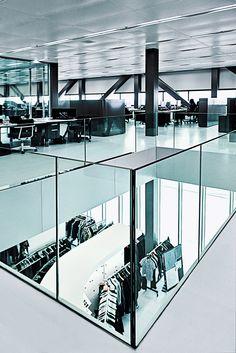 【G-STAR RAW(アムステルダム)】 オランダのデニムメーカーG-STAR RAWのオフィスは、アムステルダムの中心部の環状道路沿いにある。航空機のハンガーを意識したデザインのそのオフィスは、140メートルの長さ、2万7500平方メートルの大きさをもつ。レム・コールハースの事務所OMAが設計を担当しており、威圧感のあるコンクリートフレームにガラスのボックスが並んでいて、それを巨大な柱脚が支えているような設計になっている。外光にあふれた、柔軟性の高い内部空間には、デザインスタジオ、サンプルメーカー、ショールームが相互にコミュニケーションしやすい形で配置されている。
