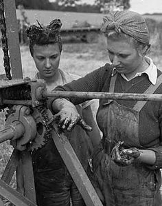 Land girls working on a combine harvester at harvest time. Joan Terrell who is greasing the machine used to be a hairdresser and Evelyn Lendon, the driver, was a typist, 1943, UKI