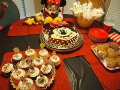 Cake Table with Home made Minnie cake,oatmeal cookies,cupcakes with toppers made out of stickers and Marshmallow pops