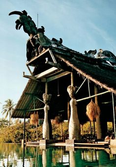 Lombok-Antique Hindu statues stand guard over the expansive pool. via Conde Nast
